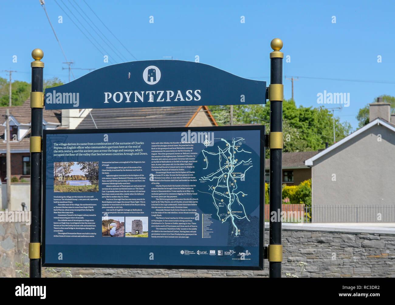 Northern Ireland village information sign at Poyntzpass, County Down, Northern Ireland. - Stock Image