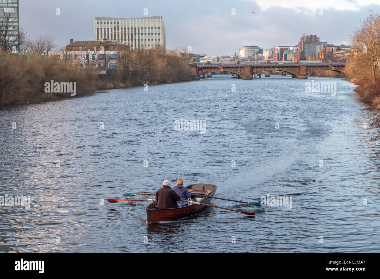 Glasgow, Scotland, UK. 13th January, 2019. UK Weather: George Parsonage of The Glasgow Humane Society and a companion rowing on the River Clyde on a day of sunshine and showers. Credit: Skully/Alamy Live News - Stock Image