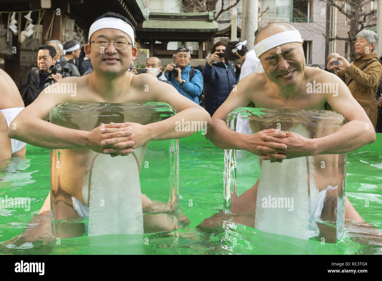 Tokyo, Japan. 13th Jan, 2019. Participants dressed only in loincloths hold two blocks of ice in a pool of freezing-cold water during the annual midwinter-ice water bathing (Kanchu-Suiyoku) purification ceremony at Teppozu Inari Shrine. About 91 brave participants (11 women) joined the purification ritual to pray for a healthy new year. Credit: Rodrigo Reyes Marin/ZUMA Wire/Alamy Live News - Stock Image