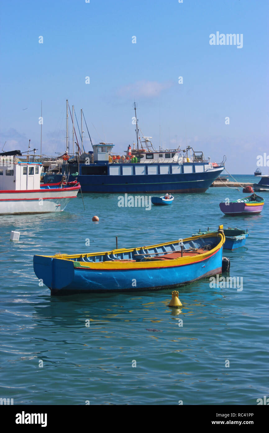 traditional fishing boats lying in the harbor of Marsaxlokk, at the south coast of Malta - Stock Image