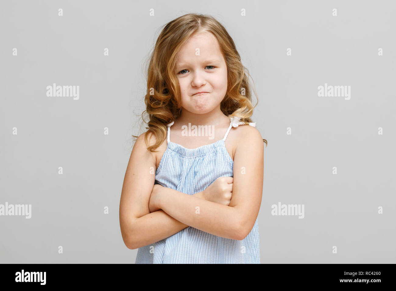 Portrait of a little girl on a gray background. Child is angry - Stock Image