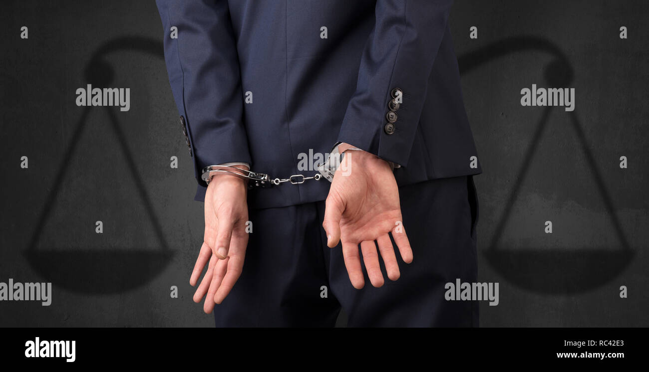 Arrested businessman in handcuffs with hands behind back and justice symbol wallpaper  - Stock Image