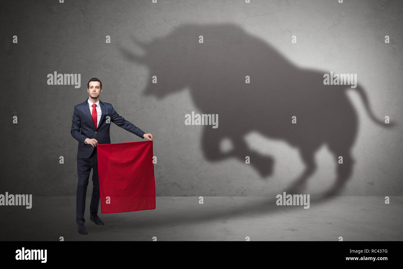 Businessman standing with red cloth in his hand and big bull shadow on the wall  - Stock Image