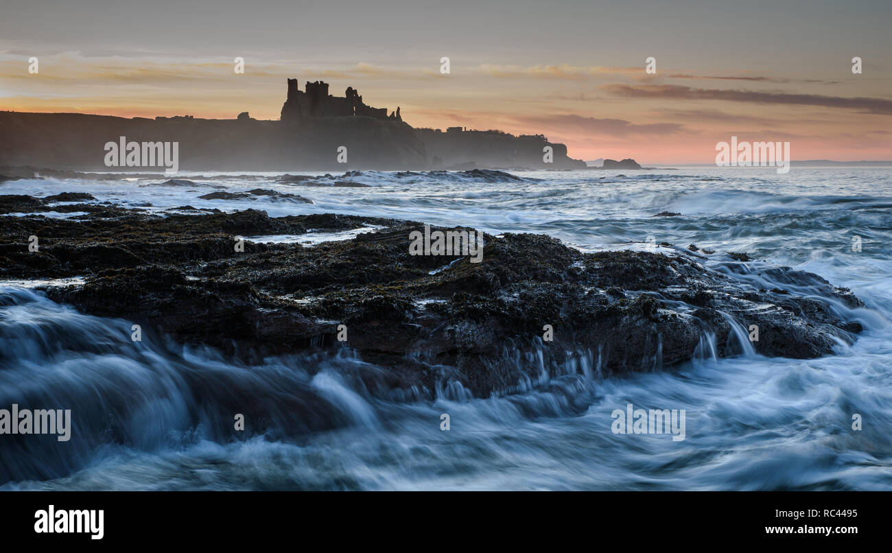 Setting sun colours the sky behind the castle where the North Sea creates motion and add complexity to the image - Stock Image