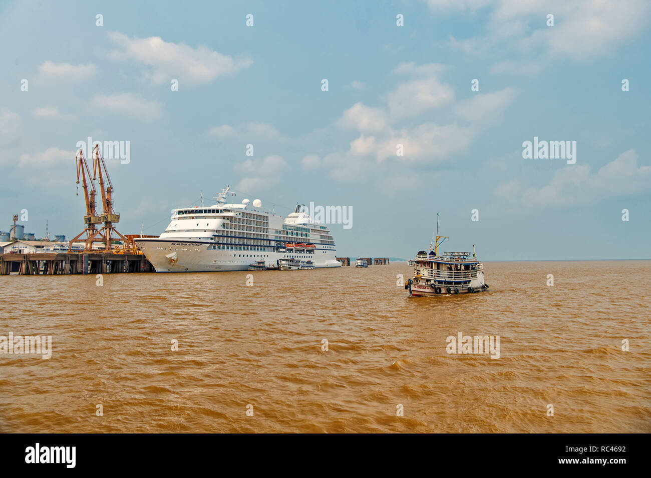 Santarem, Brazil - December 02, 2015: Seven Seas Navigator cruise liner in dock and small ship floating on sea on grey sky background. Luxury lifestyle concept. Tourist destination and travelling - Stock Image