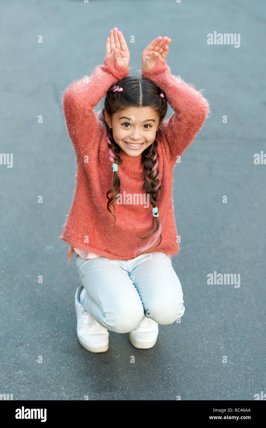 Happy easter. Holiday bunny girl posing like rabbit grey background. Child smiling play bunny role. Playful baby celebrate easter. Spring holidays. Talent and acting. Happy childhood. Cute bunny. - Stock Image