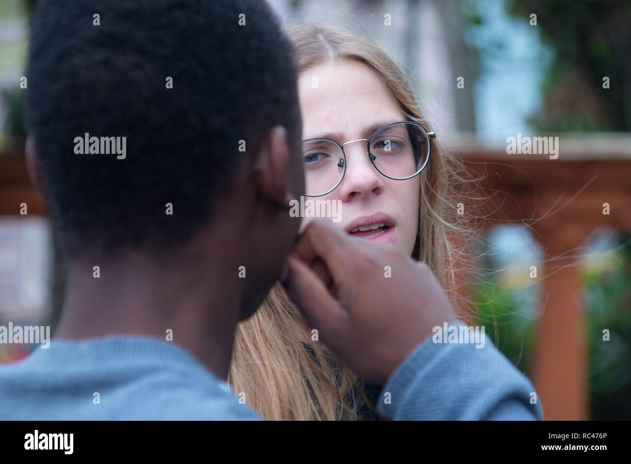A photo of two students talking to each other in a park - Stock Image