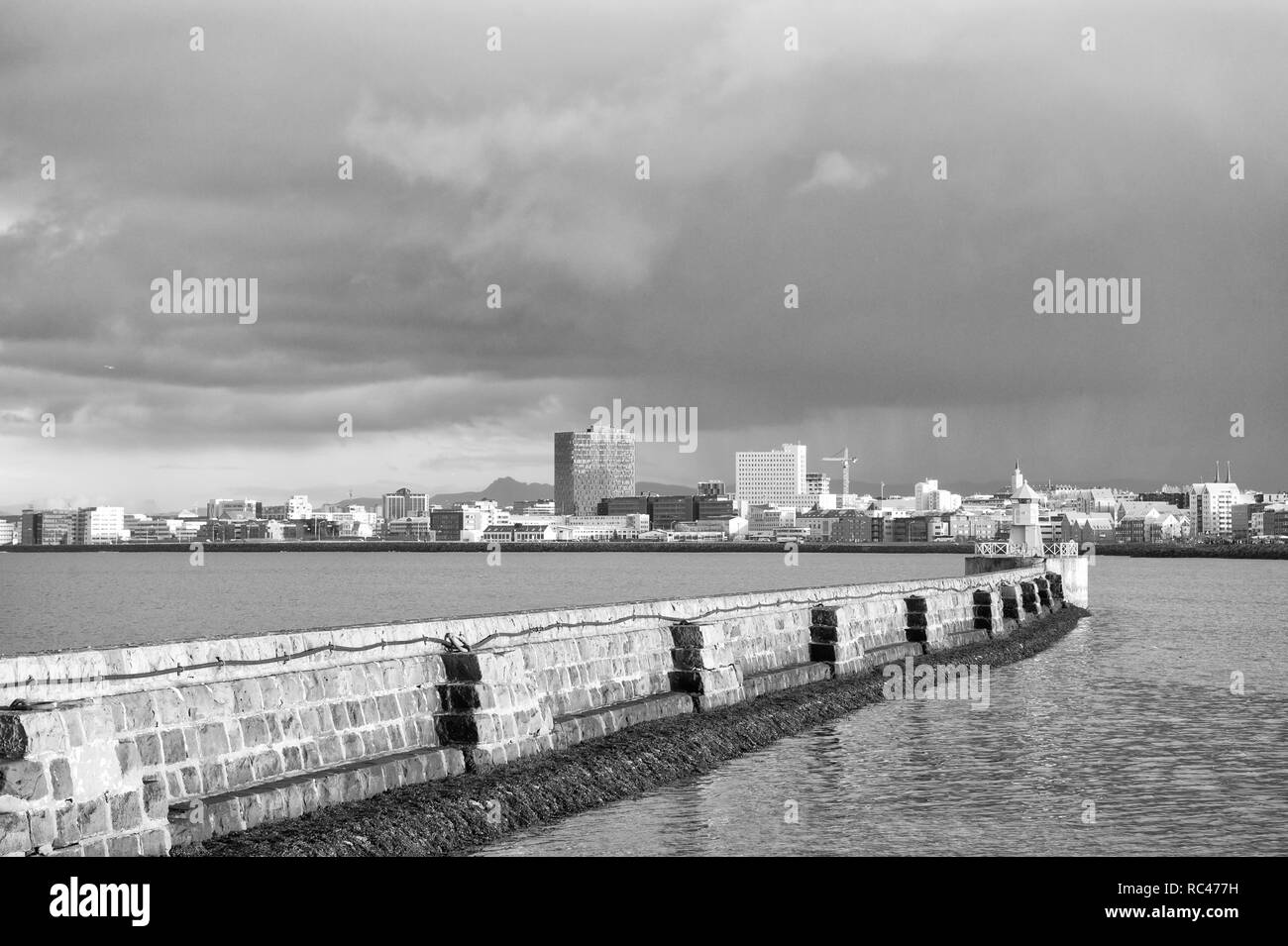 Lighthouse on sea pier in reykjavik iceland. Lighthouse yellow bright tower at sea shore. Seascape and skyline with bright lighthouse. Sea port navigation concept. Sea transportation and navigation. - Stock Image