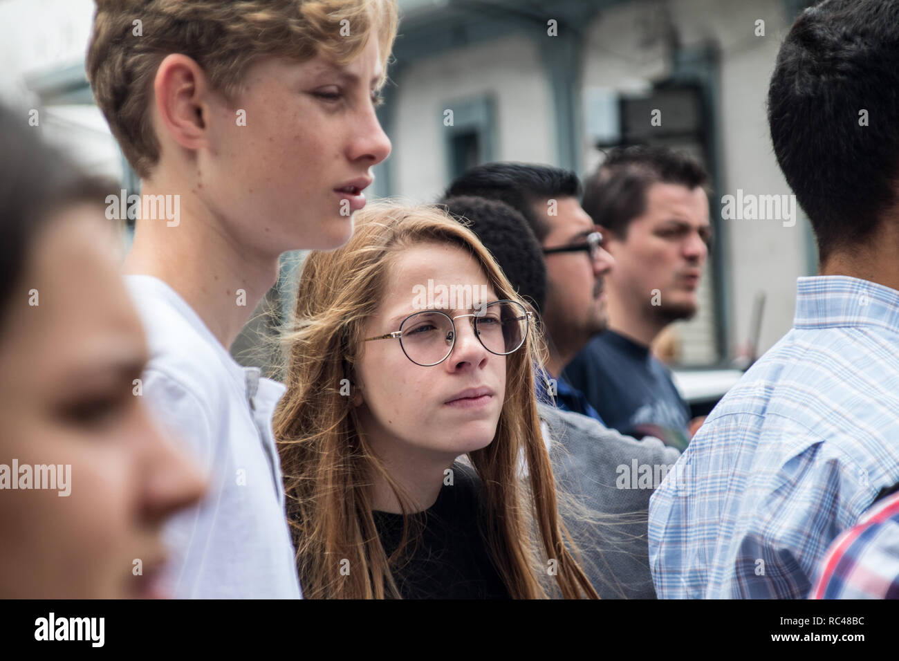 A portrait of boy and a girl walking on a crowded street - Stock Image