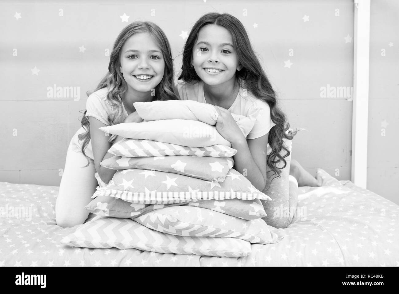 Best friends forever. Girls children on bed with cute pillows. Pajamas party concept. Girls just want to have fun. Girlish secrets honest and sincere. Friends kids have nice time pleasant leisure. - Stock Image