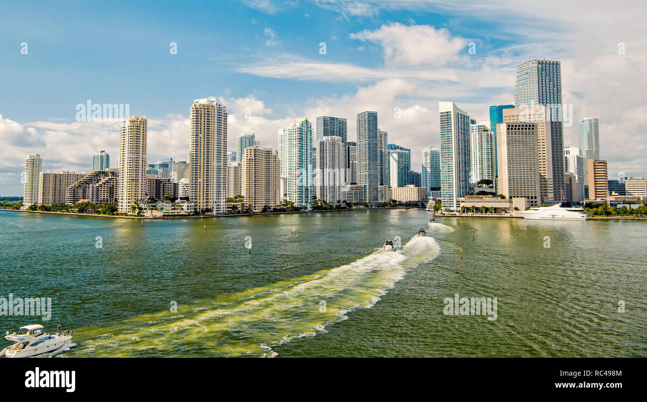 miami skyline. Yachts sail on sea or ocean water to city skyscrapers on cloudy blue sky in Miami, USA. Summer vacation, wanderlust, travelling, lifestyle concept. - Stock Image