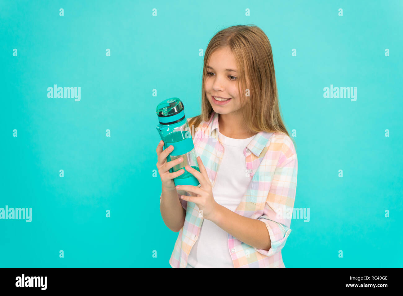 Kid hold bottle blue background. Child girl long hair has water bottle. Water balance concept. Healthy and hydrated. Pediatric disorders of water balance. Girl cares about health and water balance. - Stock Image
