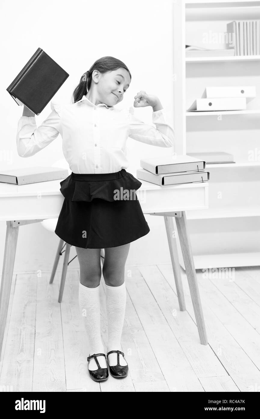 Girl child hold book while stretching white interior. Kid school uniform making exercise stretching increase productivity. Exercises to maintain vivacity. Role of active breaks in educational process. - Stock Image