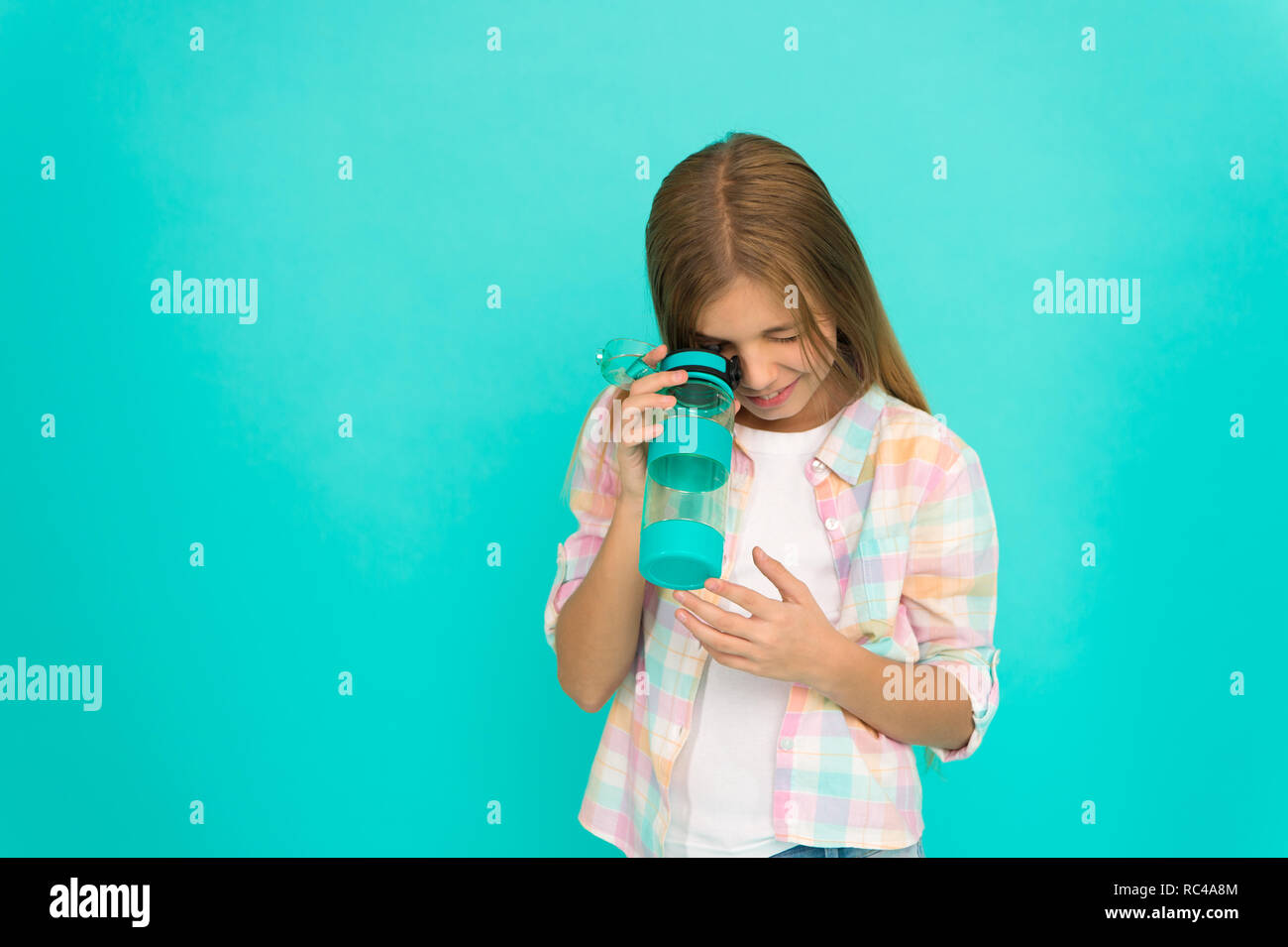 Girl cares about health and water balance. Kid hold bottle blue background. Child girl long hair has water bottle. Water balance concept. Healthy and hydrated. Pediatric disorders of water balance. - Stock Image
