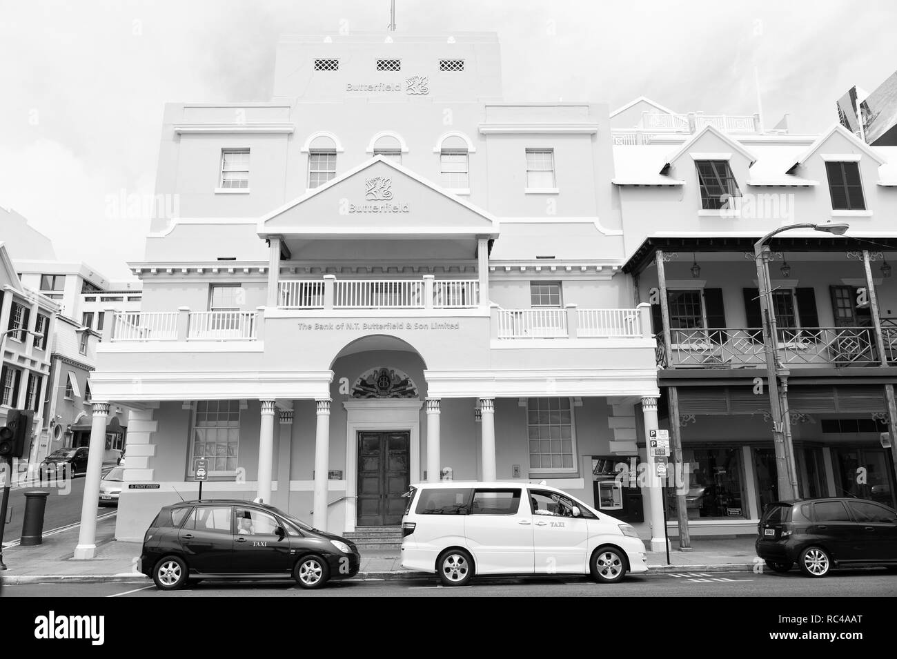 Hamilton, Bermuda - March, 20, 2016: urban bank building. Cars parked at urban city houses on street road. Urban cityscape. Travelling and wanderlust. - Stock Image