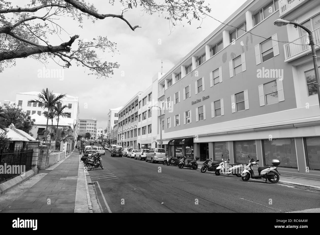 Hamilton, Bermuda - March, 20, 2016: street road. City street road. Cars and scooters parked along side of street road. Urban life. Traffic of city or street road. - Stock Image