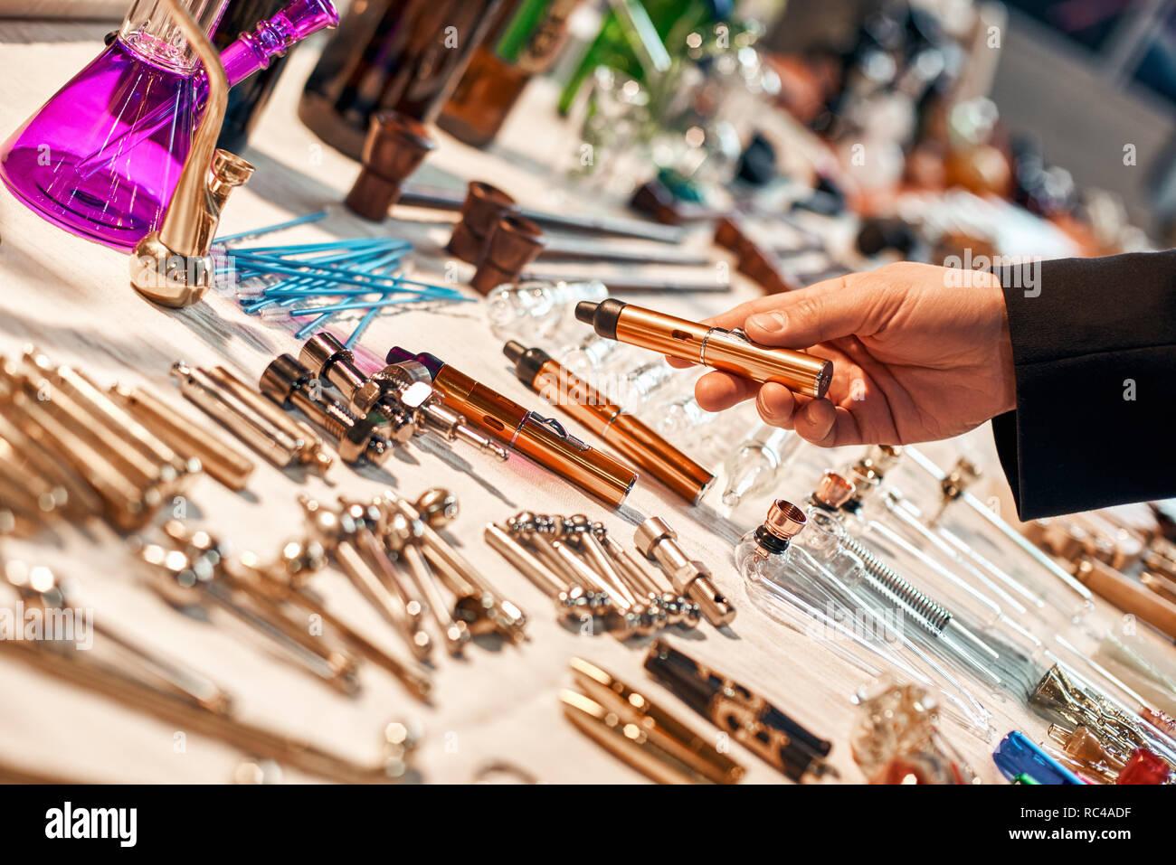 Tools for ganja handmade. Device for smoking marijuana. Items for home made device. Man's hand holding electronic vaporizer. Marijuana Electronic-Ciga - Stock Image