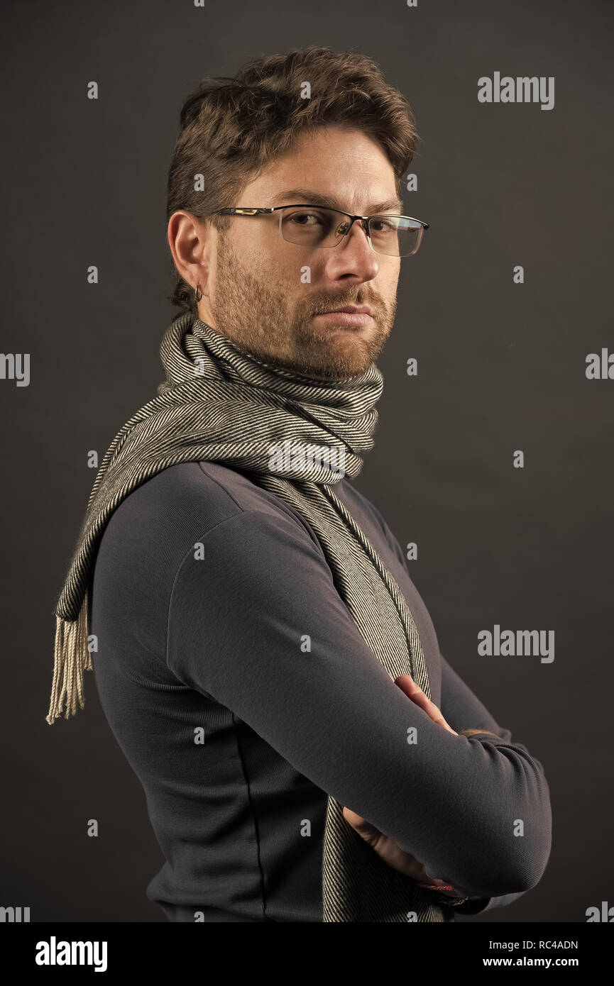 Businessman in glasses on bearded face. Fashion, eyewear, accessory. Vision, business, future concept. Eyesight correction, eye care, health. Man in scarf and sweater with folded hands - Stock Image