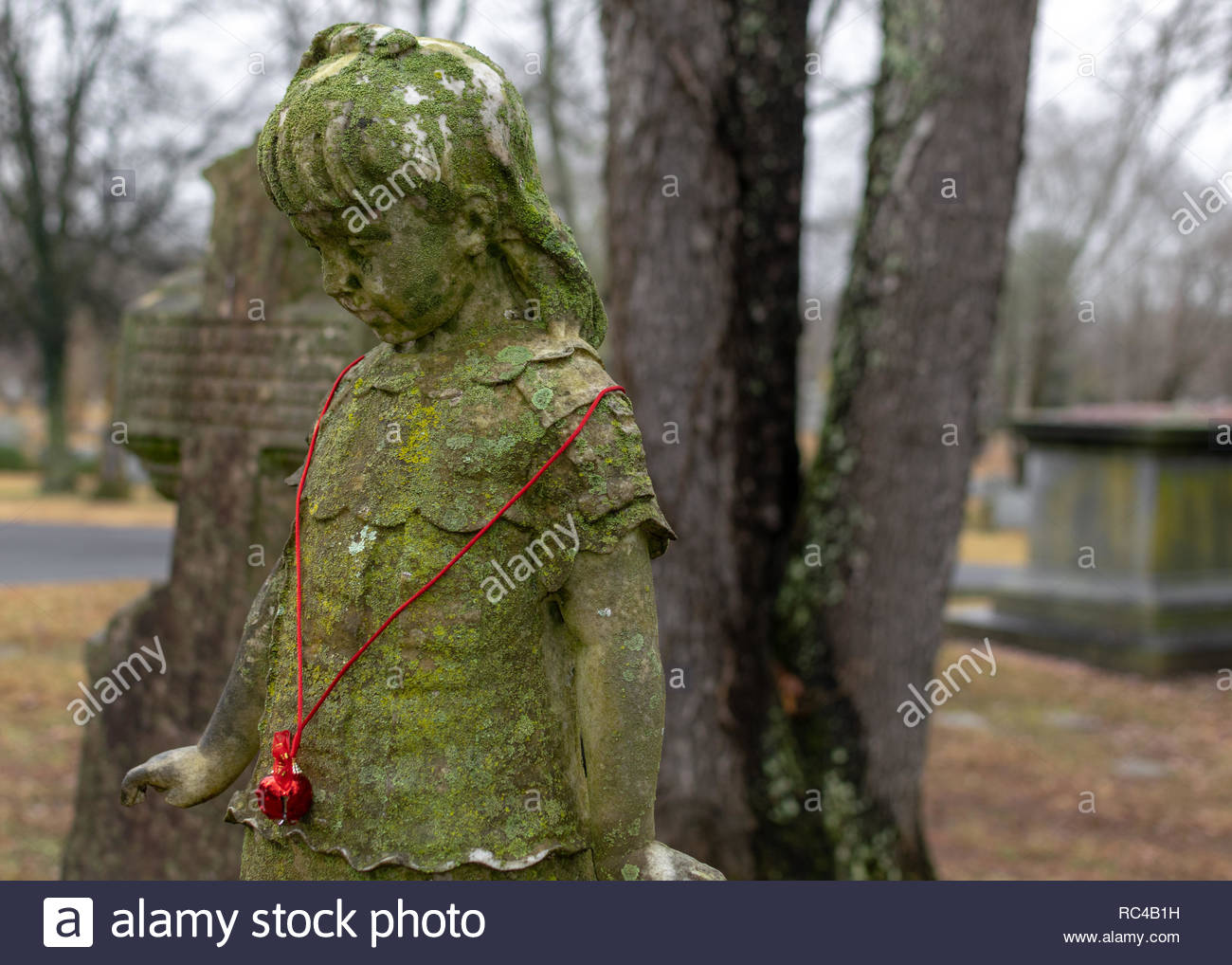 Moss covered statue of a girl wearing a Christmas bell necklace, on a grave in Greenwood Cemetery, Clarksville, Tennessee - Stock Image