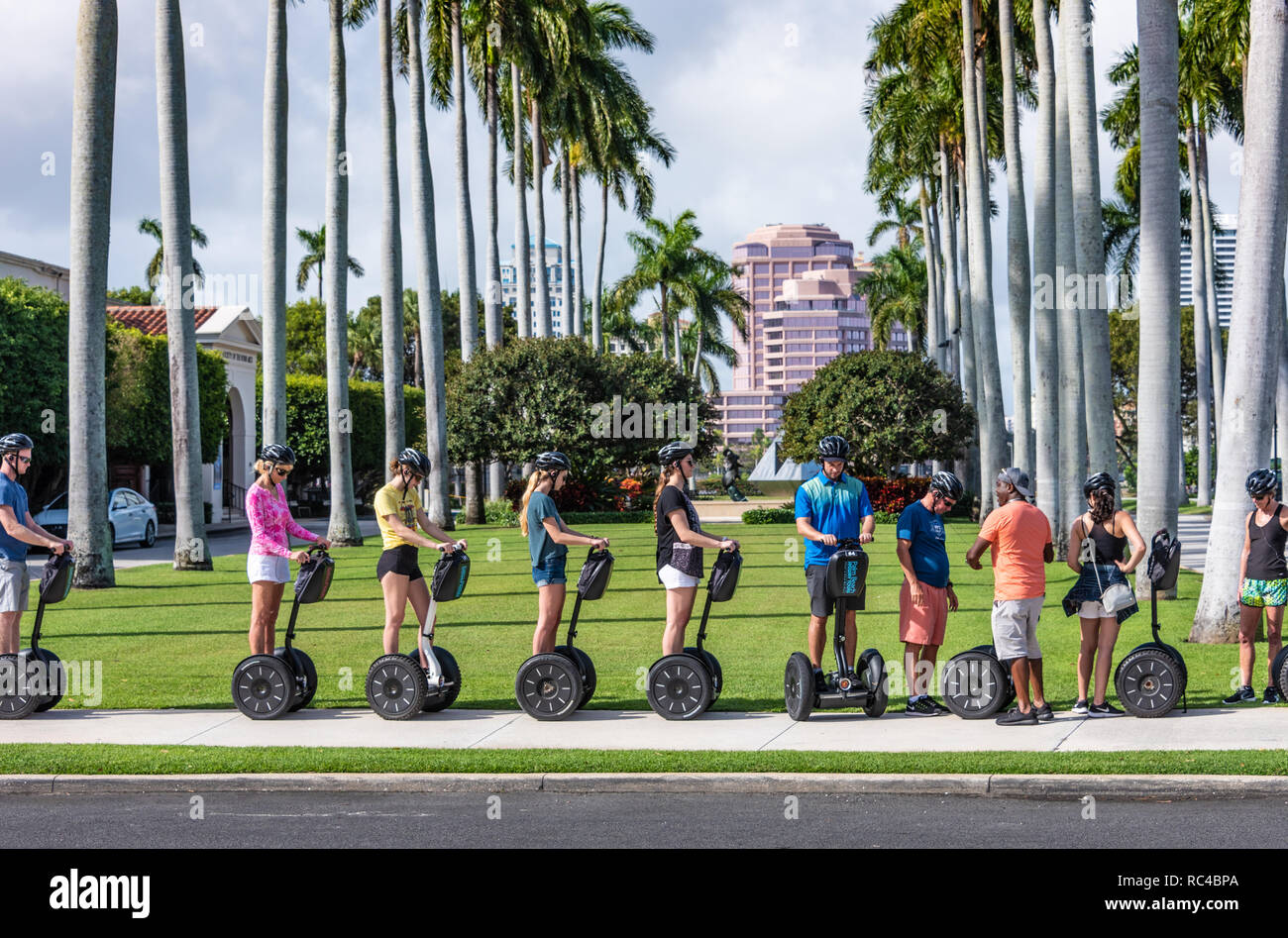 Segway tour group at the Society of the Four Arts in Palm Beach, with downtown West Palm Beach, Florida in the background. (USA) Stock Photo
