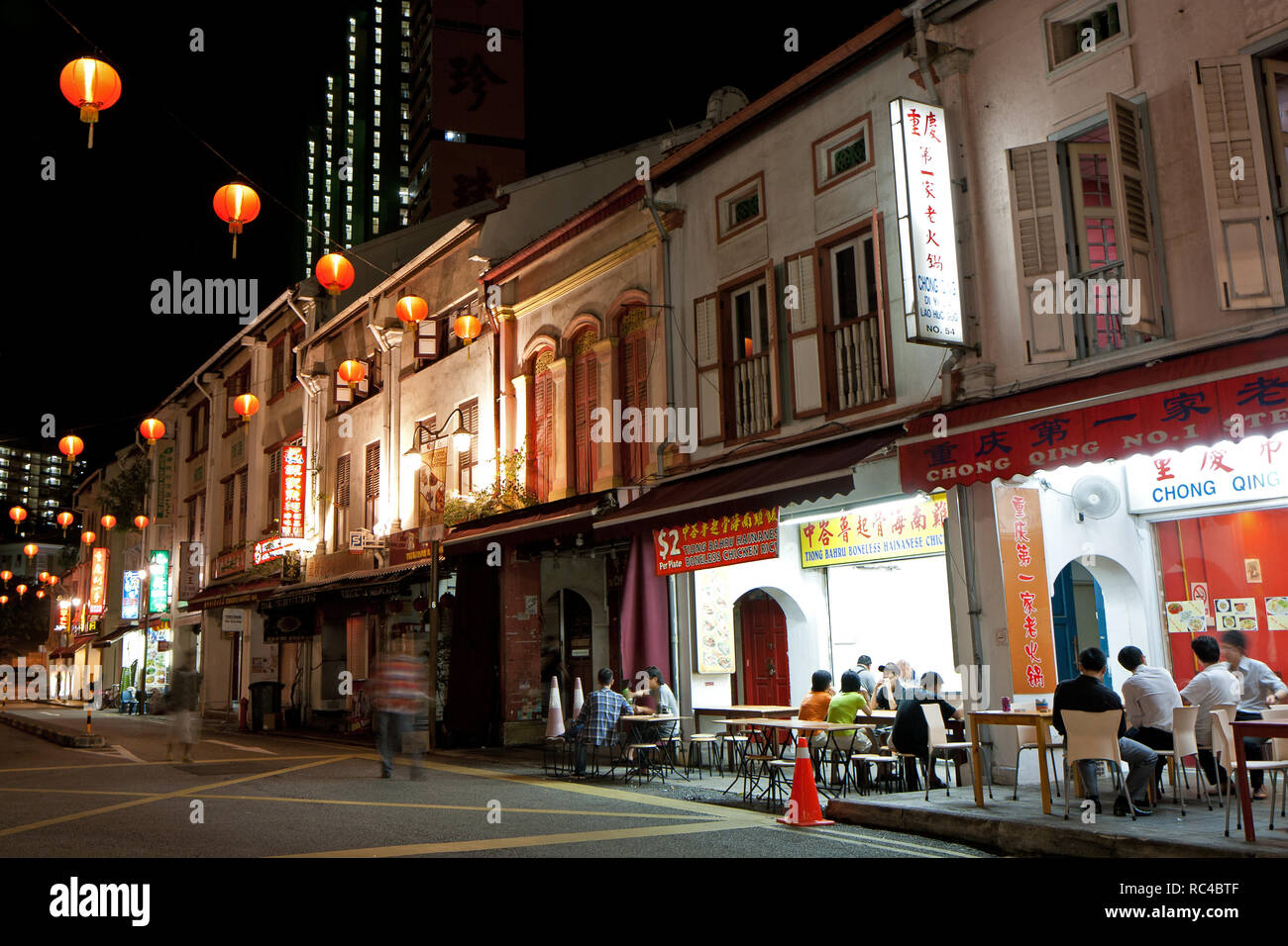 Old but renovated shophouses and few people sitting in restaurants on Smith Street in Singapore's Chinatown, at night. - Stock Image