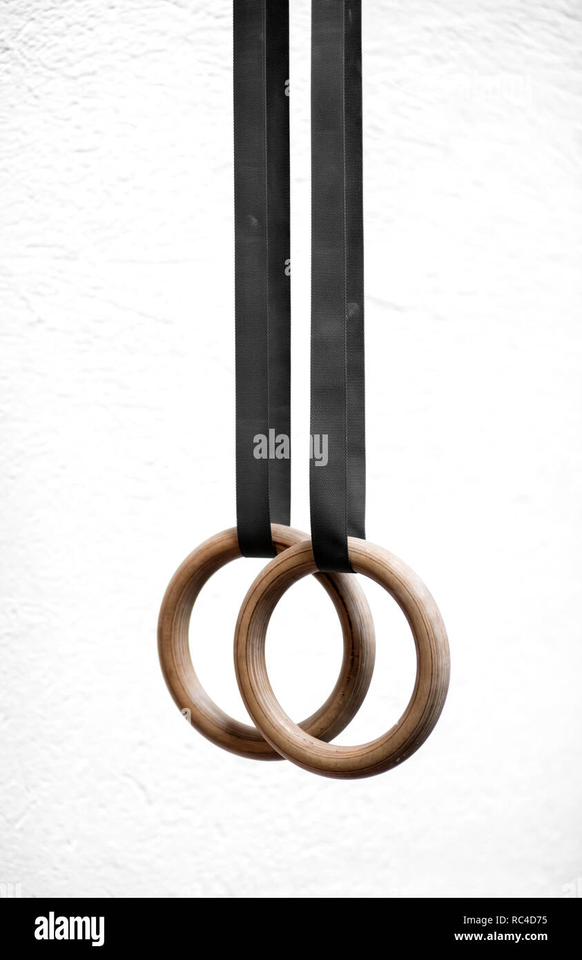 Pair of wooden sport steady rings for gymnastics, hang calmly on black straps in vertical close-up on white background - Stock Image
