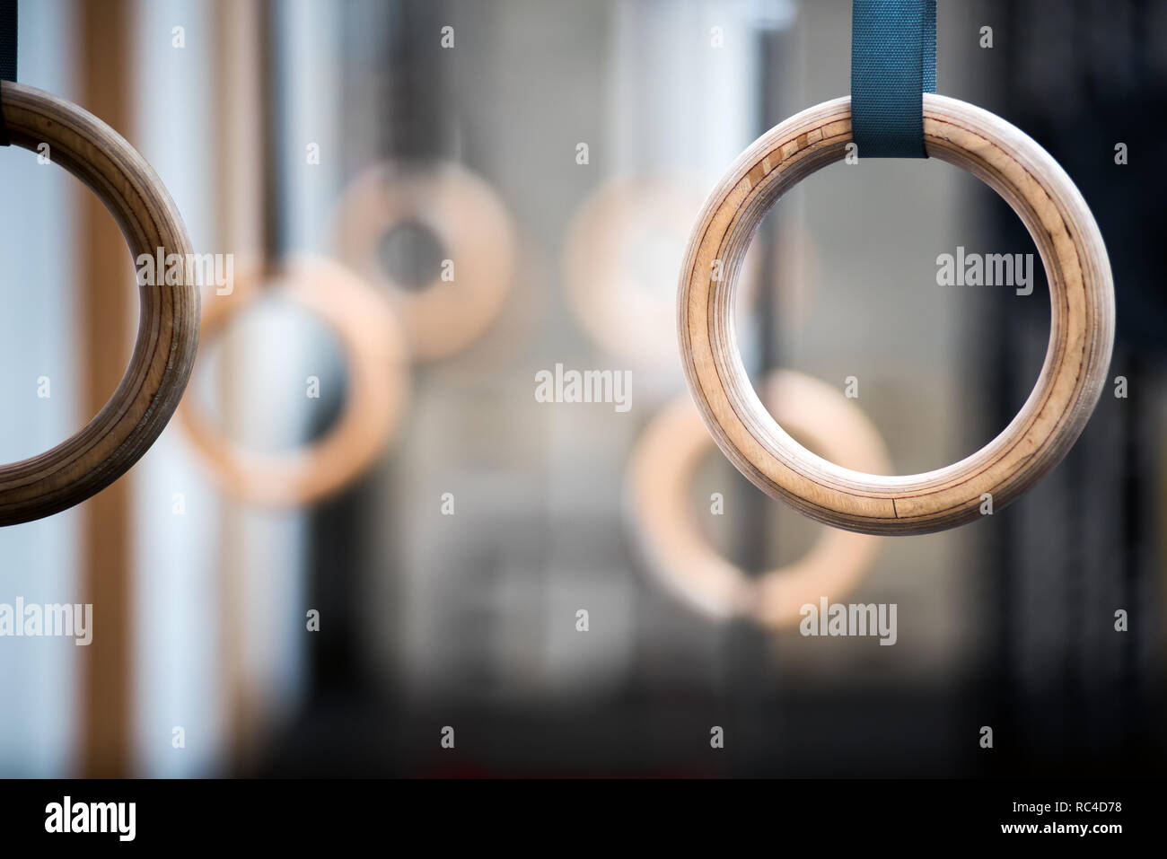 Wooden sport rings in gym, viewed in close-up with selective focus. Pair of rings is blurred in background. Gymnastics equipment concept - Stock Image