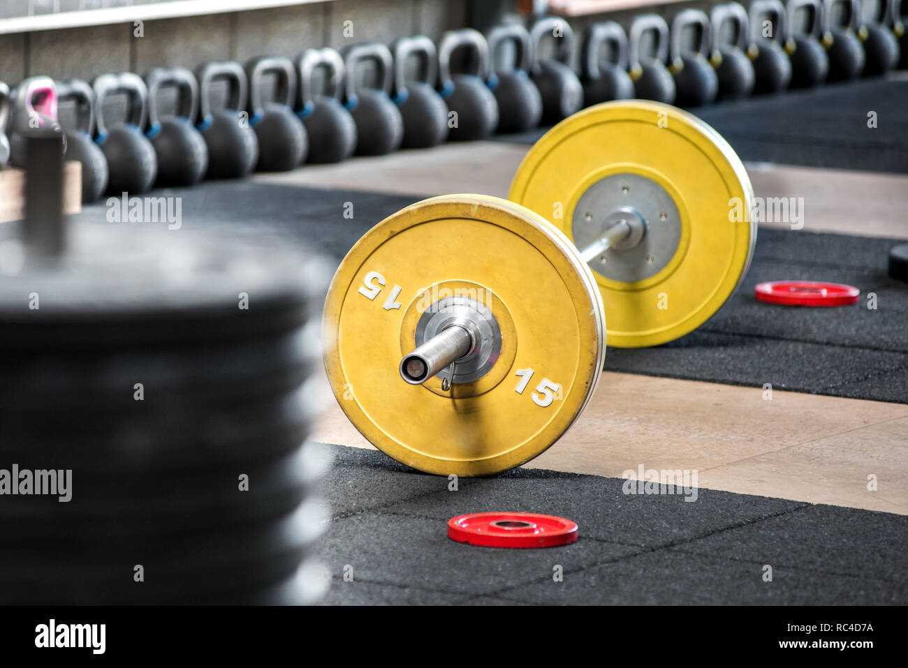 Yellow barbell on the floor in gym, viewed from the side in selective focus. Heavy weights training equipment - Stock Image