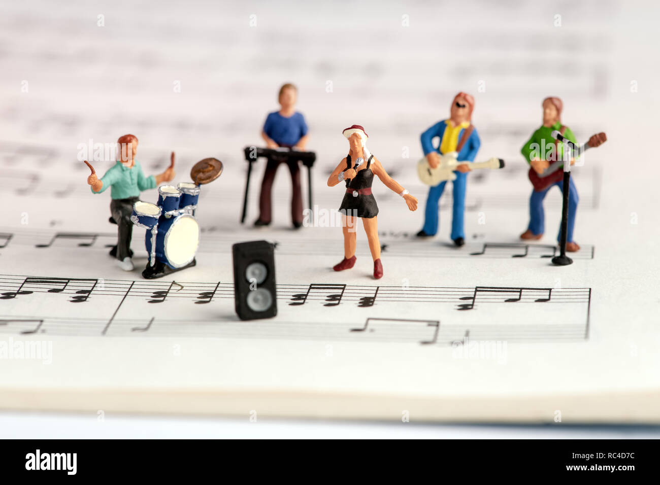 Rock band miniature people performing on open music book with notes, viewed in tilt-shift selective focus, from high angle - Stock Image