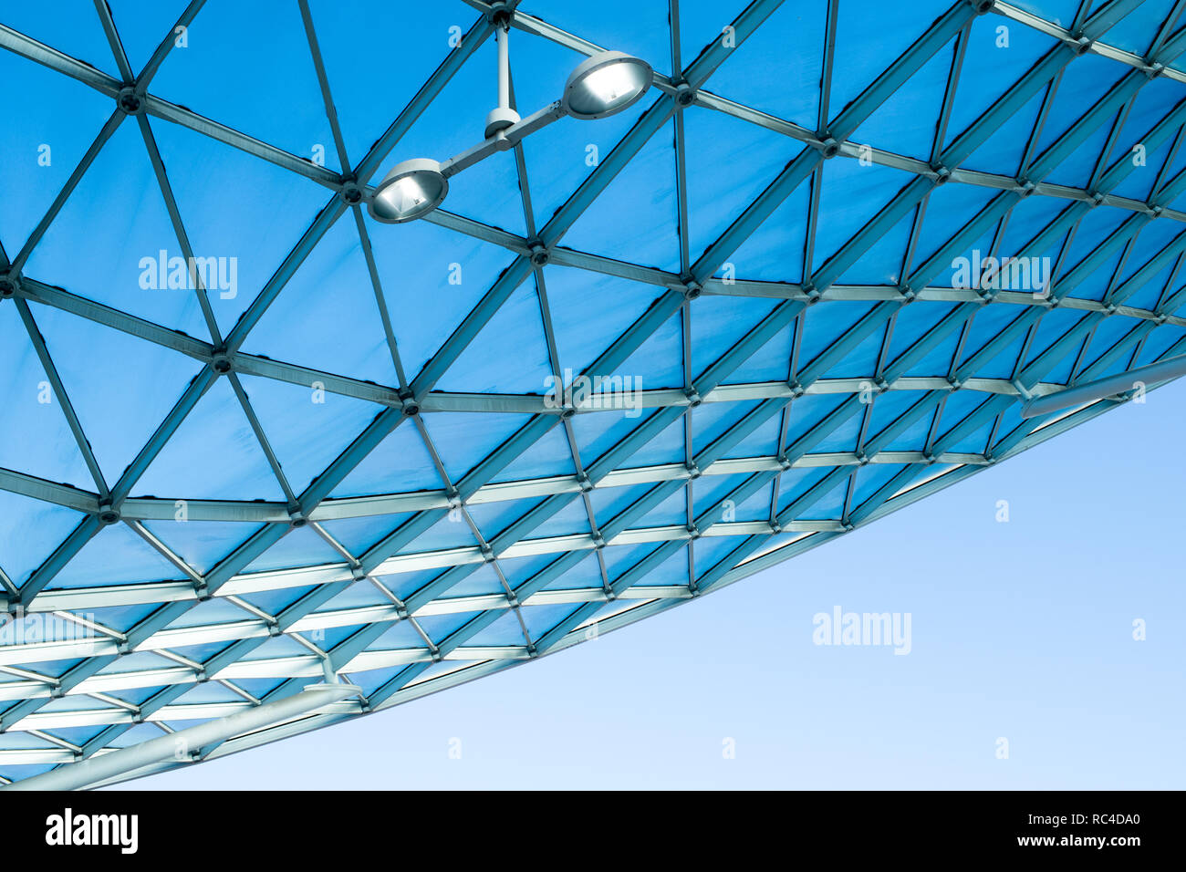 Modern architecture glass roof with curved design of steel structure. Low angle view with blue sky, indoor lighting and white wall of the building - Stock Image