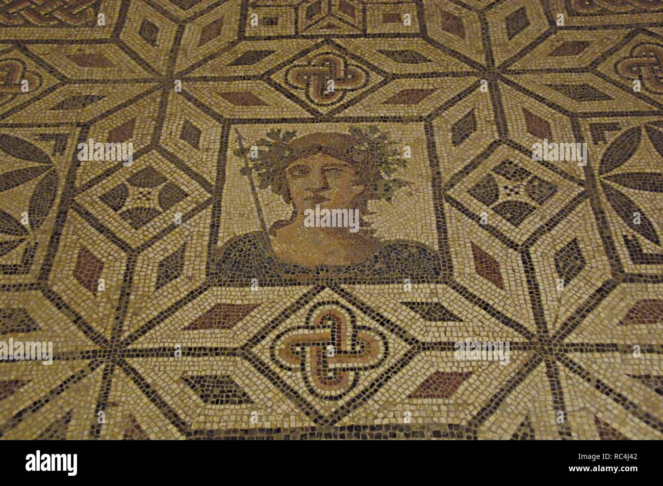 Roman Art. Spain. Mosaic of Bacchus. 2nd century A.C. It comes from Italica (Seville). Bacchus crowned with vine leaves and armed with thyrsus topped with the spearhead. Archaeological Museum of Seville. Andalusia. Stock Photo