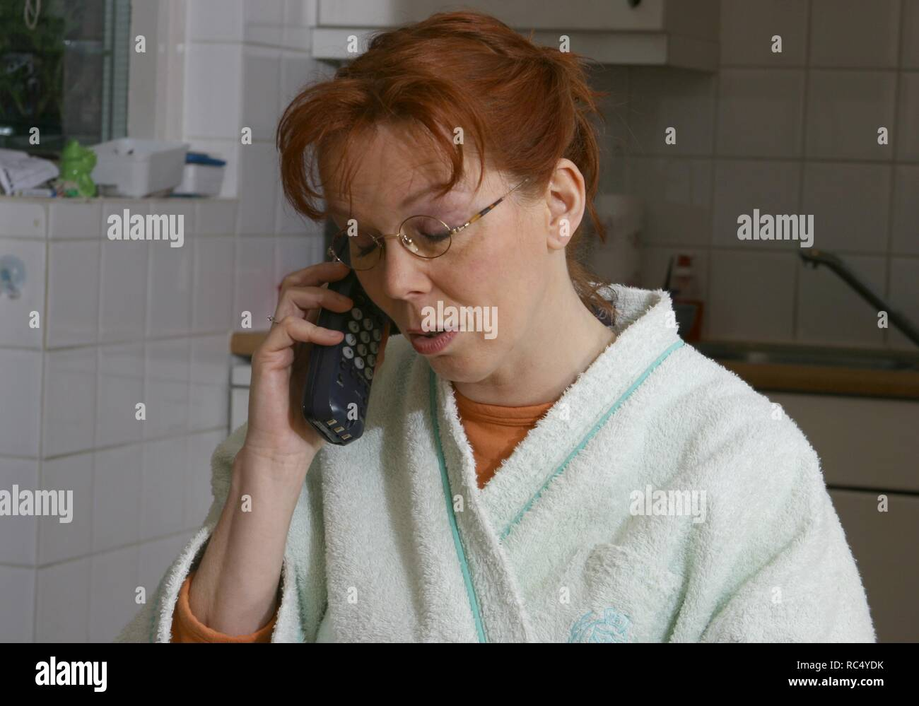 Woman in the 2000s at the breakfast table in morningcoat talking on the cordless telephone handset. - Stock Image