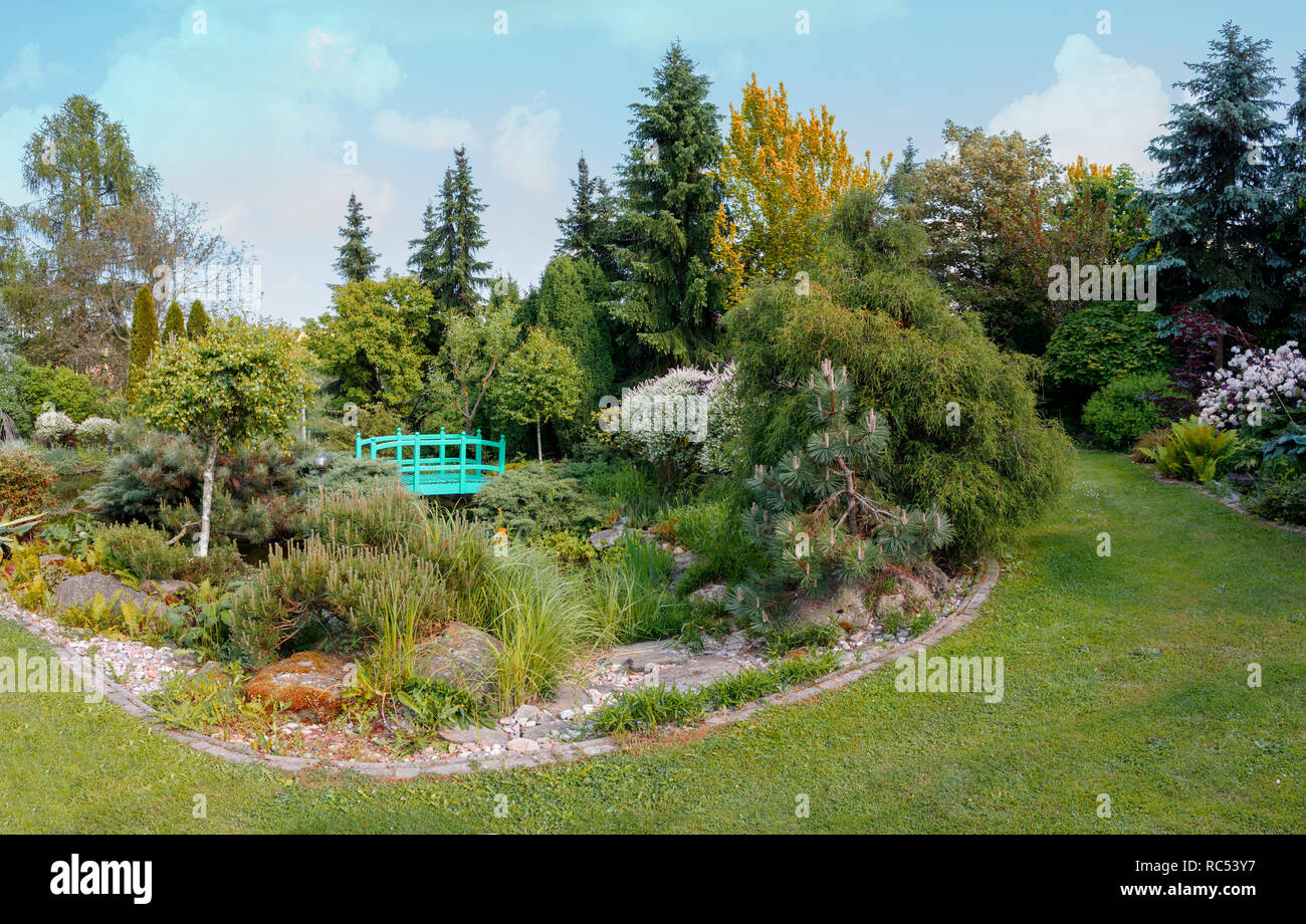 Beautiful Spring Garden With Ornamental Conifers And Small Garden