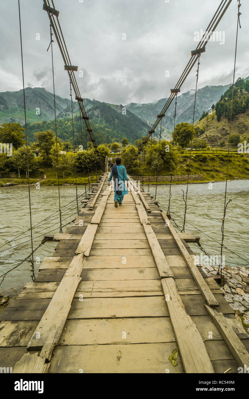 A woman crossing river Indus on dangerously looking bridge in Pakistan. - Stock Image