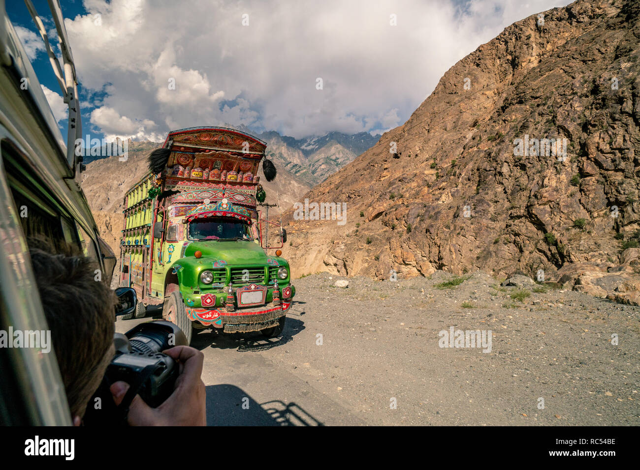 Traditional decorated truck in Pakistan on dangerous road in the mountains. - Stock Image