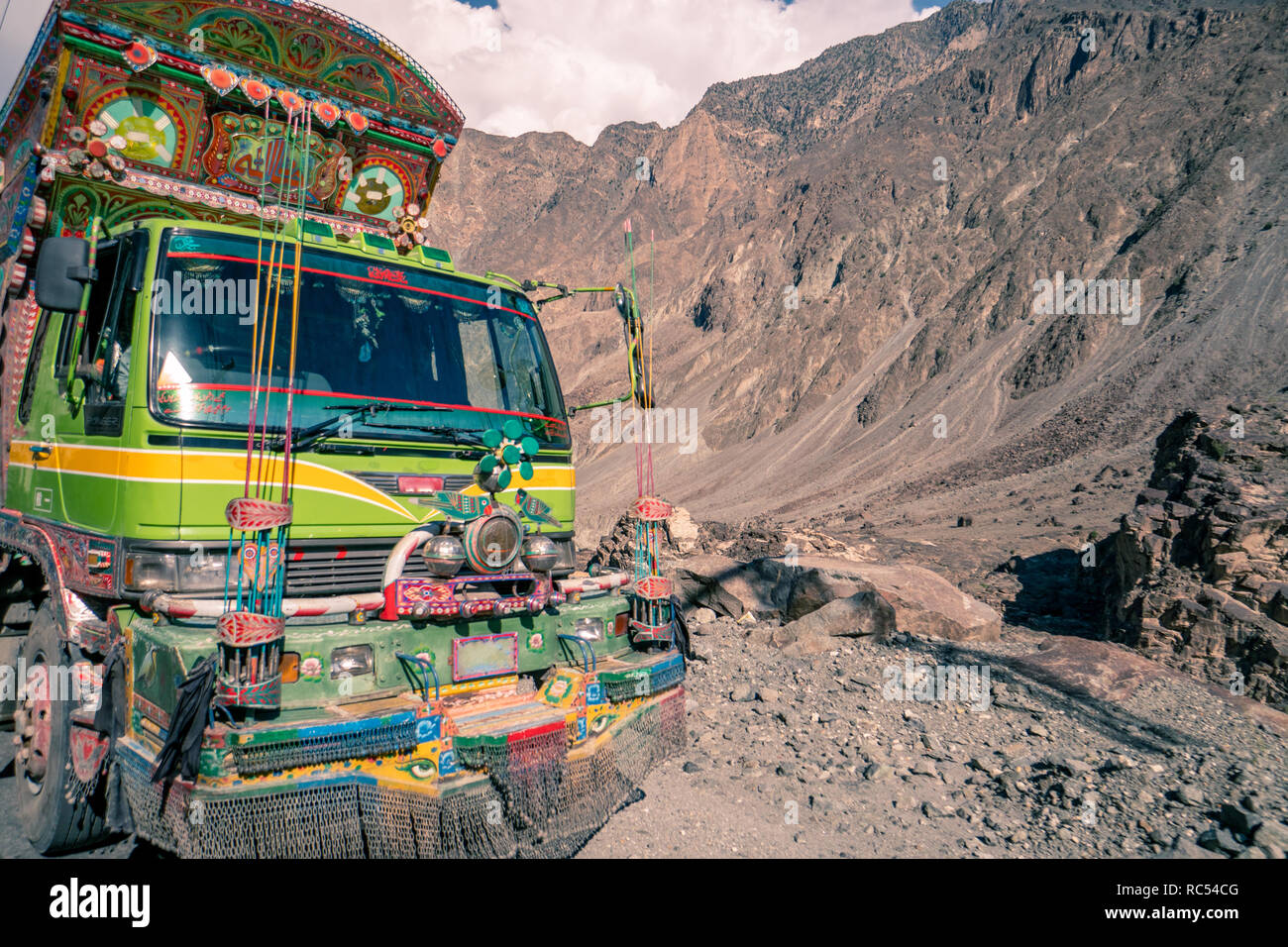 Decorated truck in Pakistan on dangerous road in the mountains. - Stock Image