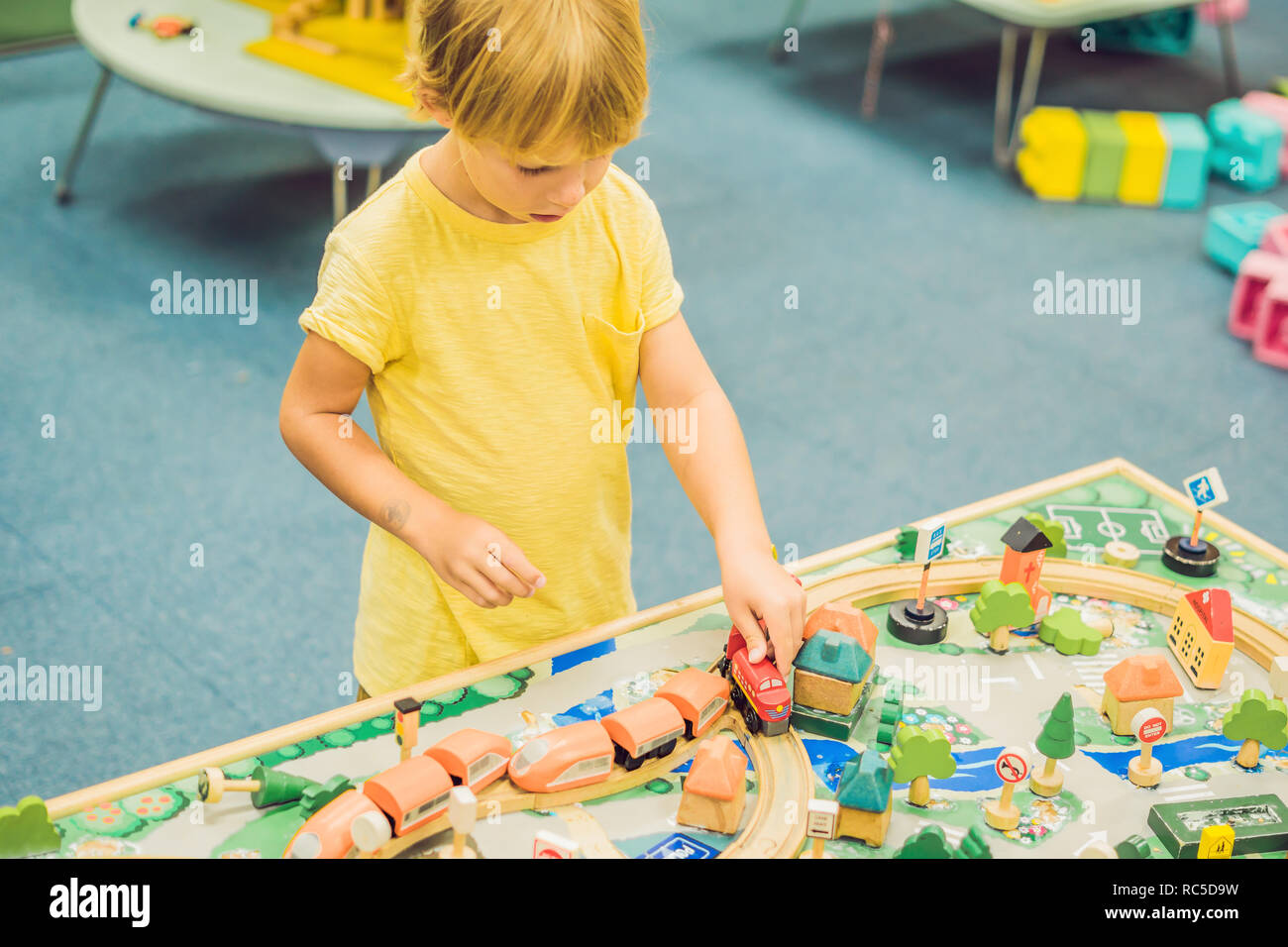 Children play with wooden toy, build toy railroad at home or daycare. Toddler boy play with crane, train and cars. Educational toys for preschool and kindergarten child. Cushioned furniture, chair bag - Stock Image