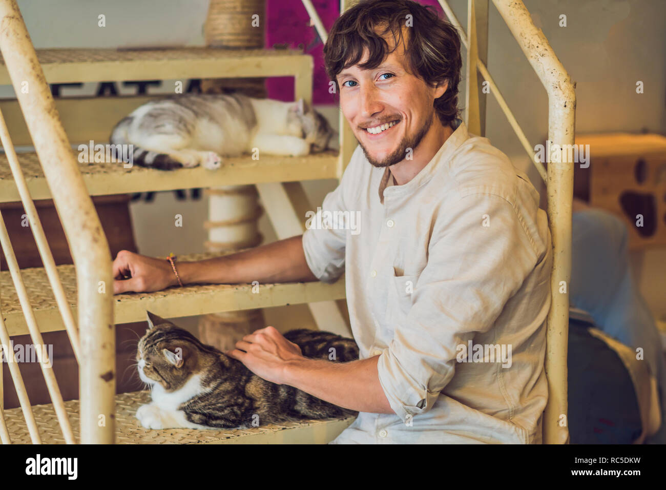 Portrait of handsome young man playing with cat and drinks coffee Stock Photo