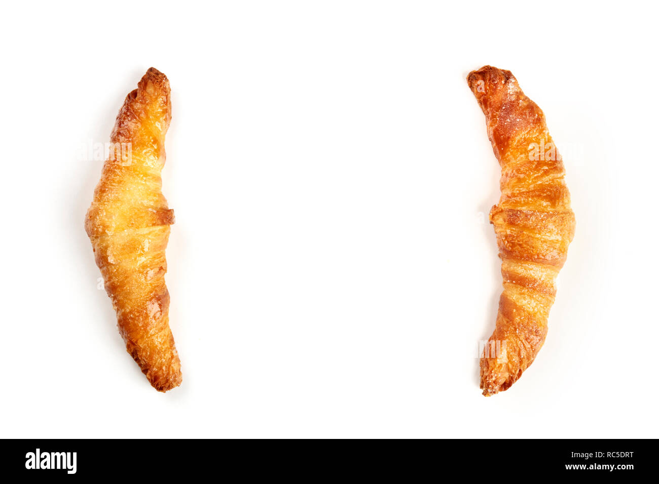 Two croissants on a white background, shot from the top, forming a frame for copy space - Stock Image