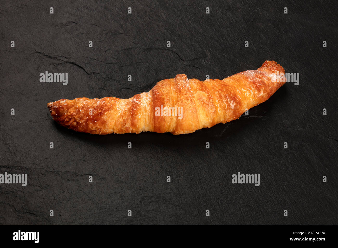 A croissant on a black background with copy space - Stock Image