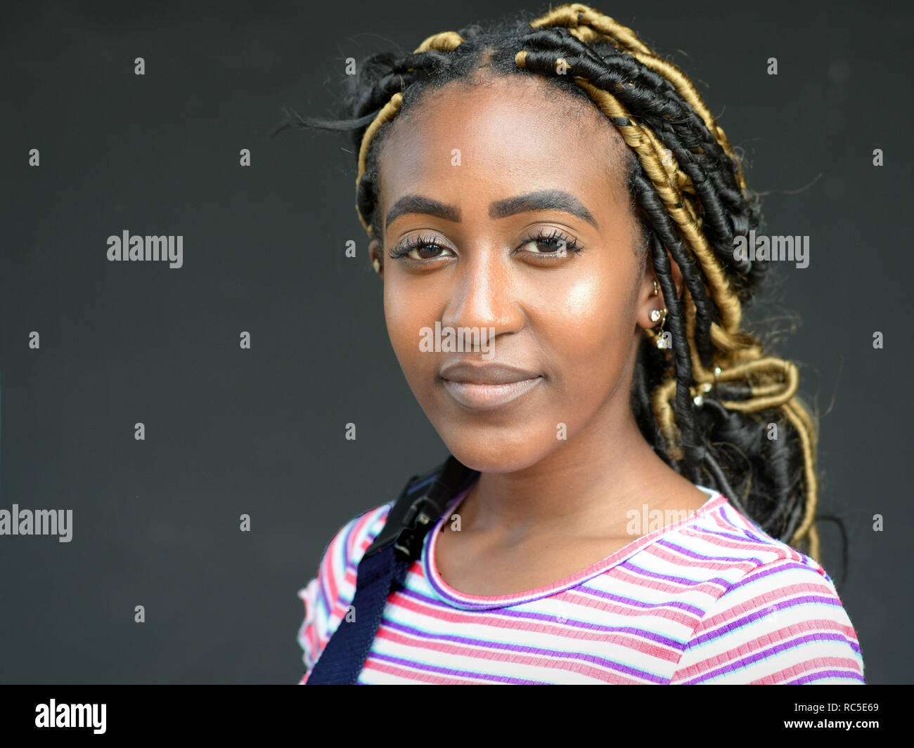 Young Afro-German beauty with blonde dyed dreadlocks poses for the camera. - Stock Image