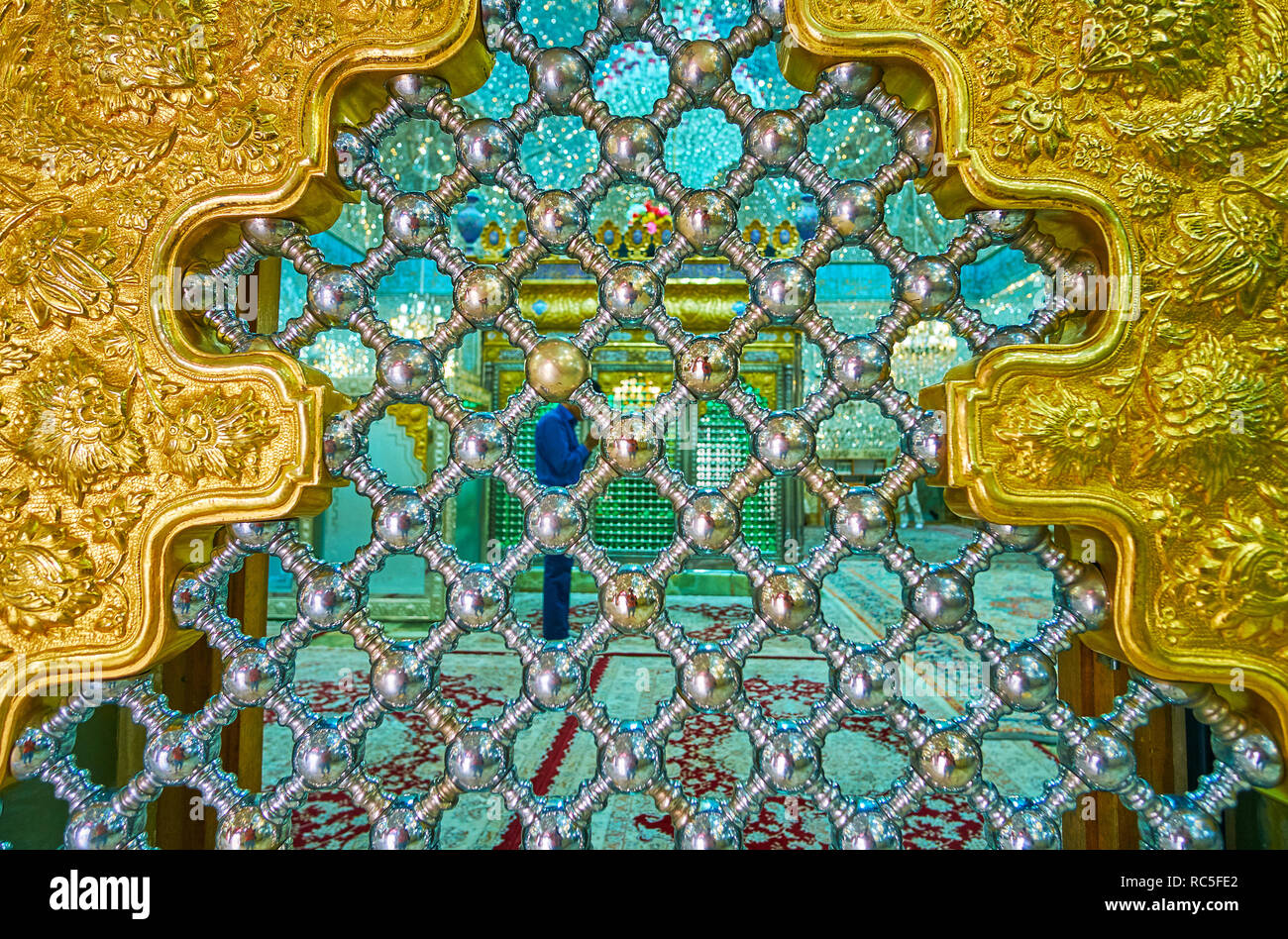 YAZD, IRAN - OCTOBER 18, 2017: The view through the shining metal lattice of the Persian screen to the men's praer hall of Imam Zadeh Jafar Shrine, on - Stock Image