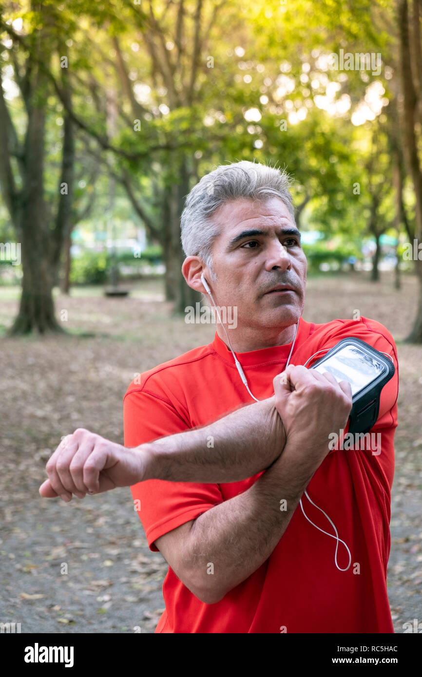 A mature man stretching in Ibirapuera park, Sao Paulo, Brazil - Stock Image