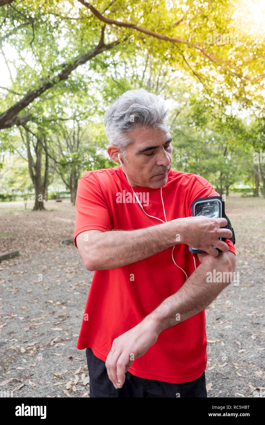 A middle-aged Latino man exercising in a park - Stock Image