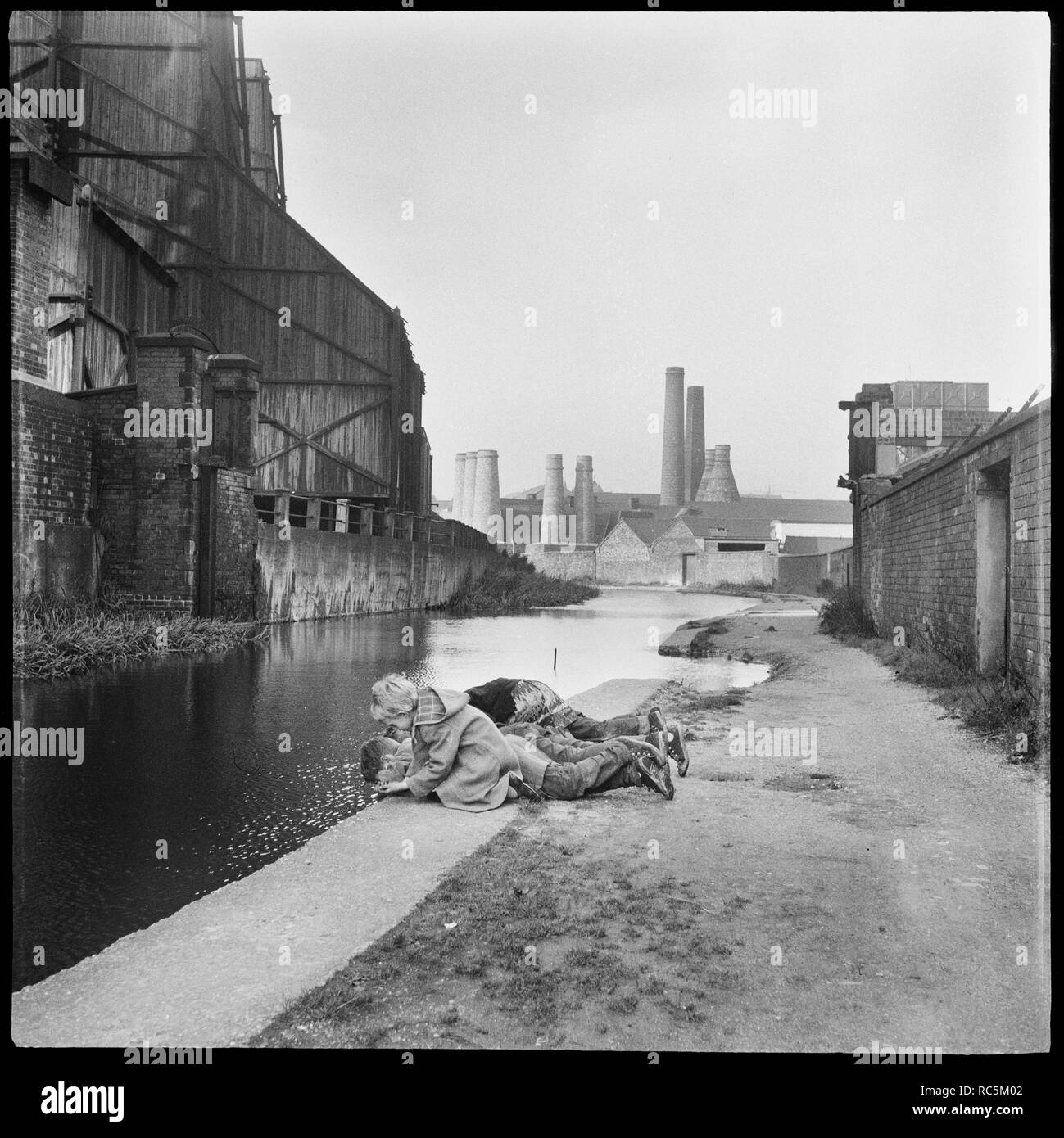 Caldon Canal, Joiner's Square, Hanley, Stoke-on-Trent, Staffordshire, 1965-1968. Children lying on the towpath looking into the waters of the Caldon Canal opposite the Electricity Works with Trent Works and Westwood Mills in the background. - Stock Image