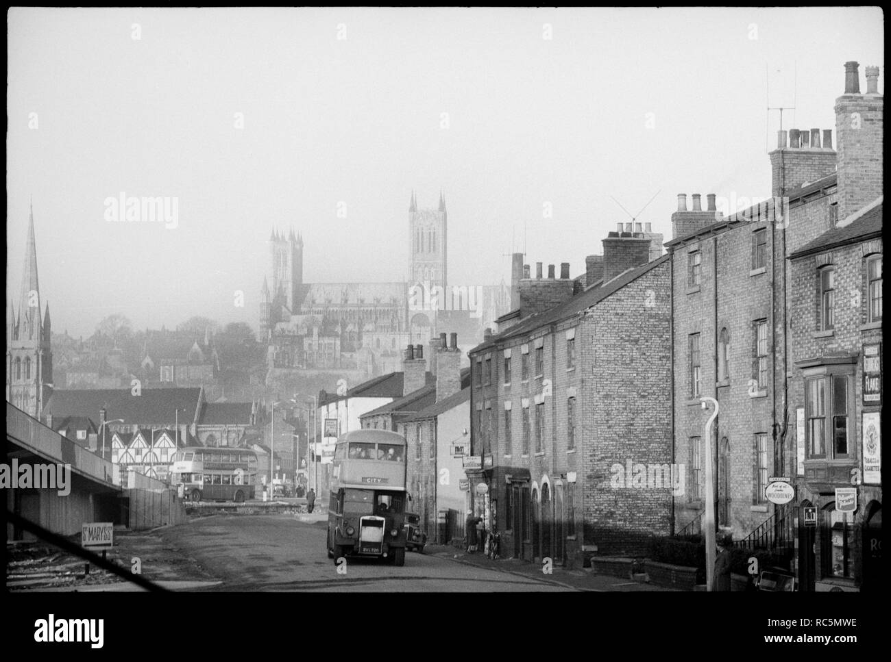 St Mary's Cathedral Church, Minster Yard, Lincoln, Lincolnshire, c1955-c1980. General view of Lincoln looking along Melville Street towards the Green Dragon Public House, with St Swithin's Church in the midground and St Mary's Cathedral Church in the background. The image shows a general view of Lincoln north of the River Witham, and shows three listed buildings amongst the rooftops. On the left side of the image, past the entrance to a road bridge is the Green Dragon public house, a timber-framed building with arch braces and a jettied top floor with four gables, three of which can be seen. P - Stock Image