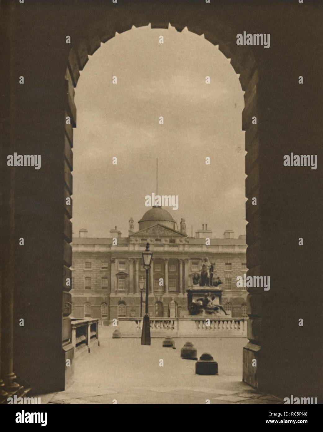 """'A Passing View of Somerset House From The Strand', c1935. Somerset House in London was built to the designs of Sir William Chambers, and was intended to house public offices: the Navy Board, the Royal Academy of Arts, the Royal Society, and the Society of Antiquaries. The foundations were laid in 1776, and completed by 1780. From """"Wonderful London, Volume 1"""", edited by Arthur St John Adcock. [The Fleetway House, London, c1935] - Stock Image"""