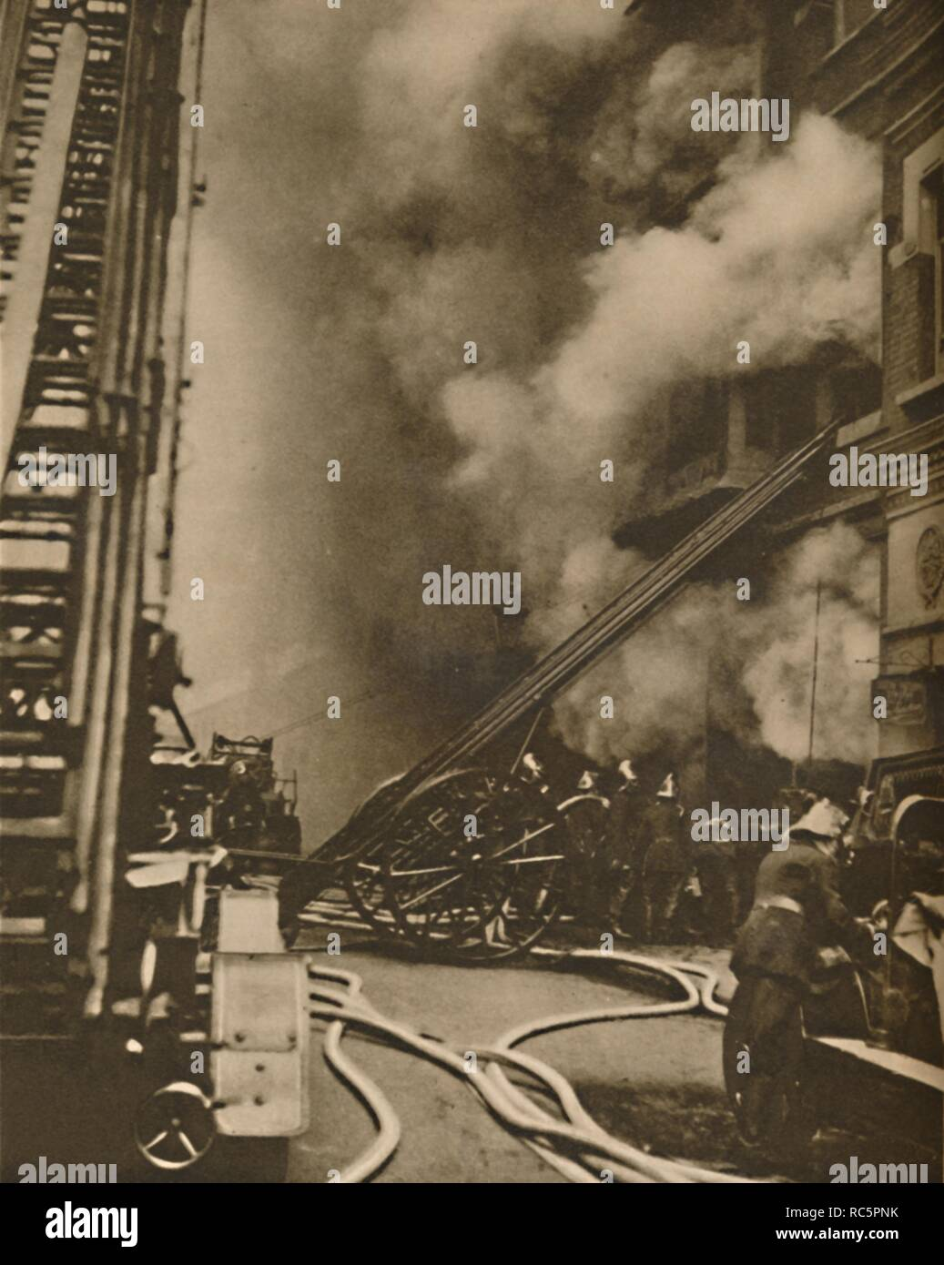"""'Subduing a Conflagration in a Narrow City Street', c1935. Fire brigade at the scene of a fire in London, with a ladder on wheels. From """"Wonderful London, Volume 1"""", edited by Arthur St John Adcock. [The Fleetway House, London, c1935] - Stock Image"""