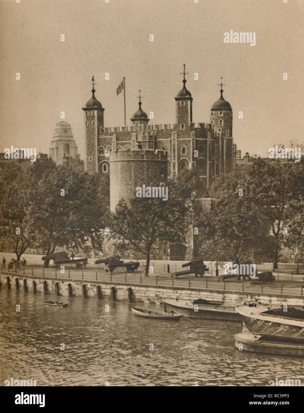 "'London's Oldest and Newest Public Buildings from Tower Bridge', c1935. The White Tower - built by William the Conqueror during the early 1080s - seen from the River Thames, with cannon on the bank and barges in the foreground. To the left is the Port of London Authority building at Tower Hill, designed by Sir Edwin Cooper and built 1912-1922. From ""Wonderful London, Volume 1"", edited by Arthur St John Adcock. [The Fleetway House, London, c1935] - Stock Image"