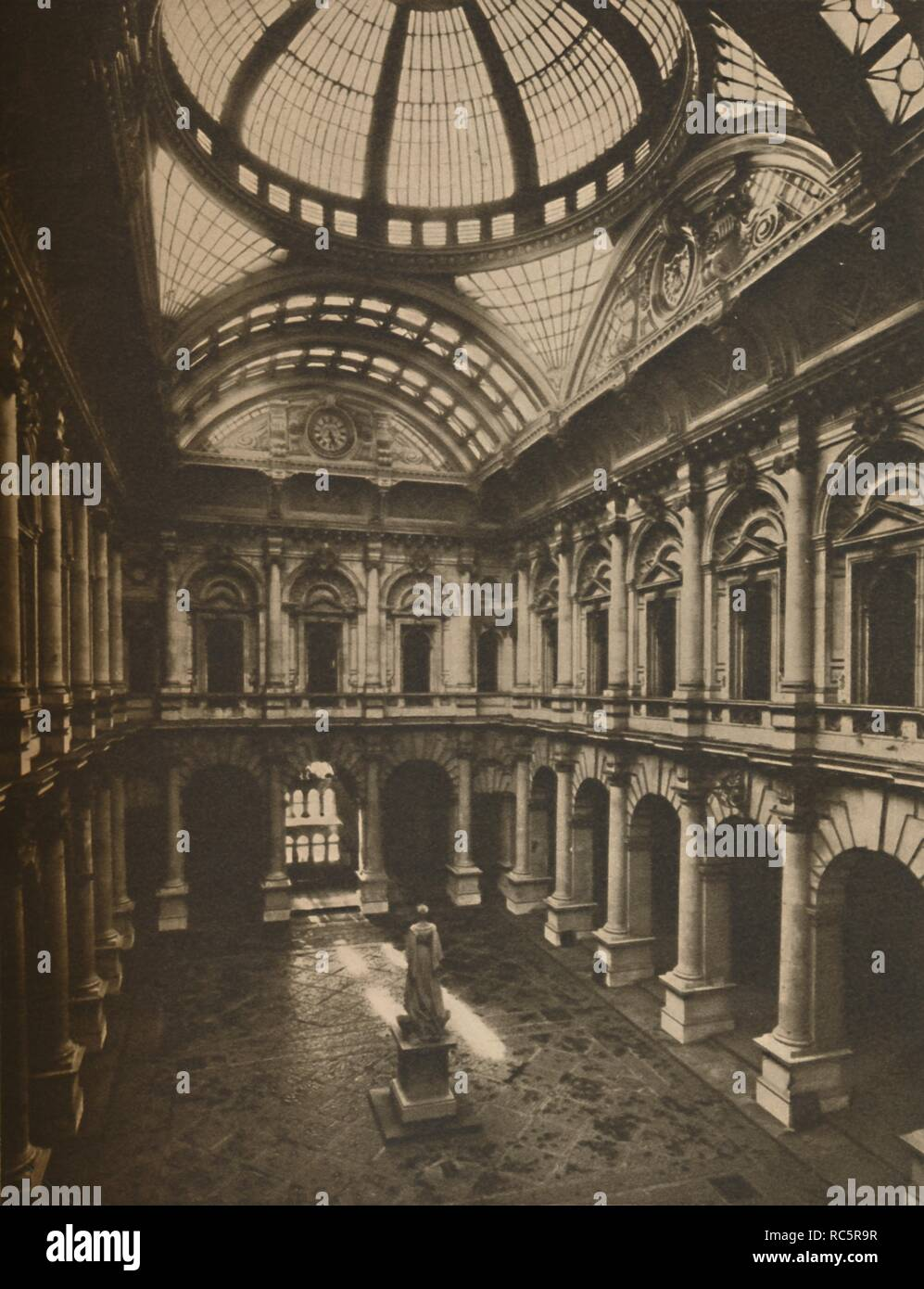 "'Glass-Roofed Interior Court of the Royal Exchange', c1935. The Royal Exchange was founded in the 16th century by the merchant Thomas Gresham on the suggestion of his factor Richard Clough to act as a centre of commerce for the City of London. The current building, designed by William Tite, was built in the 1840s. From ""Wonderful London, Volume 3"", edited by Arthur St John Adcock. [The Fleetway House, London, c1935] Stock Photo"